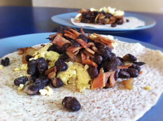 Image of Eggs, bacon, black beans in flour tortilla