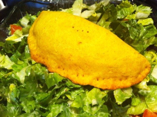 Image of Jamaican beef patty on a bed of salad